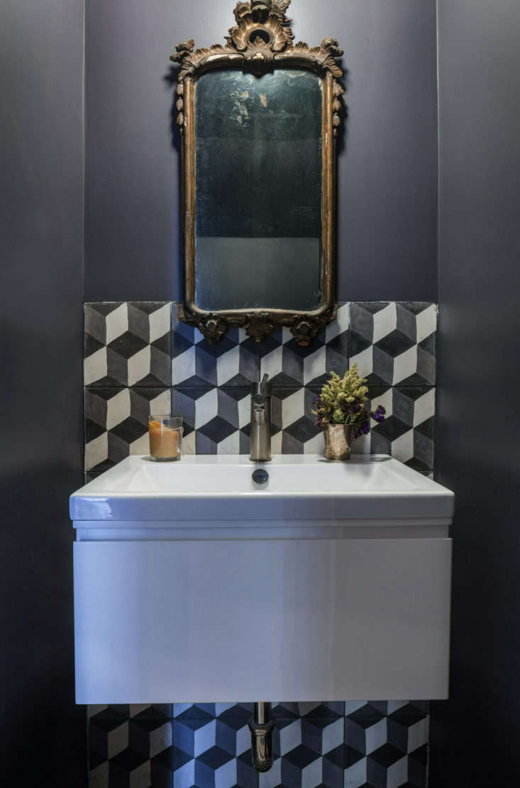 A new powder room tucked under the stairs has a cement-tiled backsplash in a pattern called Rotterdam Blocks from Granada Tile in Los Angeles. The sink is the