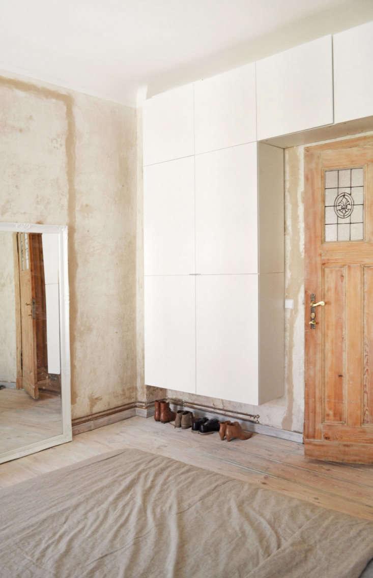 Floating built-in storage frames the bedroom door. The door&#8