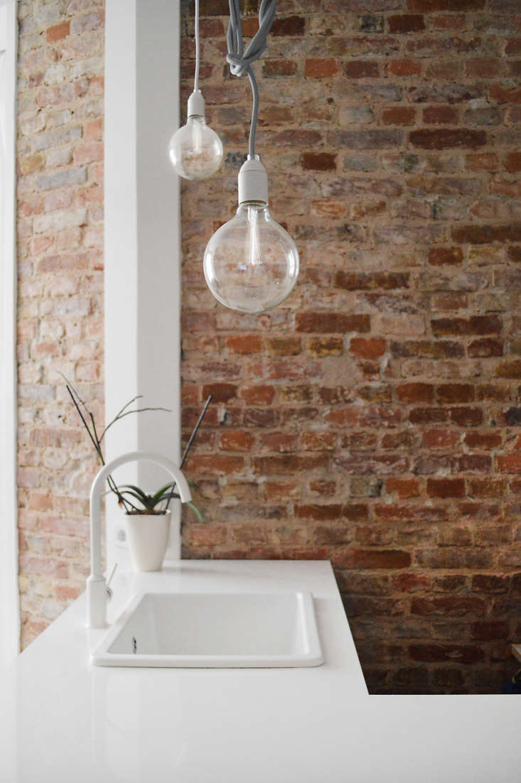 Playful modern lighting hangs above the sink. Like the all-white faucet? See  Easy Pieces: Modern Matte White Faucets for our favorites.