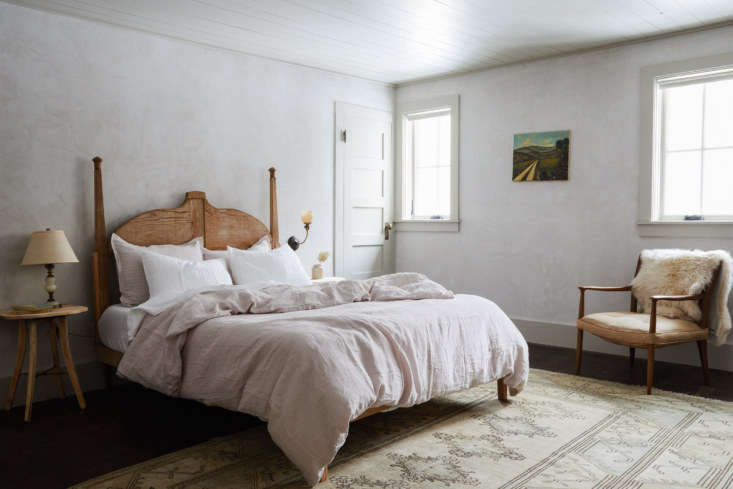 Soft gray walls plaster walls, a painted ceiling, and linen bedding byParachute Home create a luminous atmosphere in the Trung bedroom.