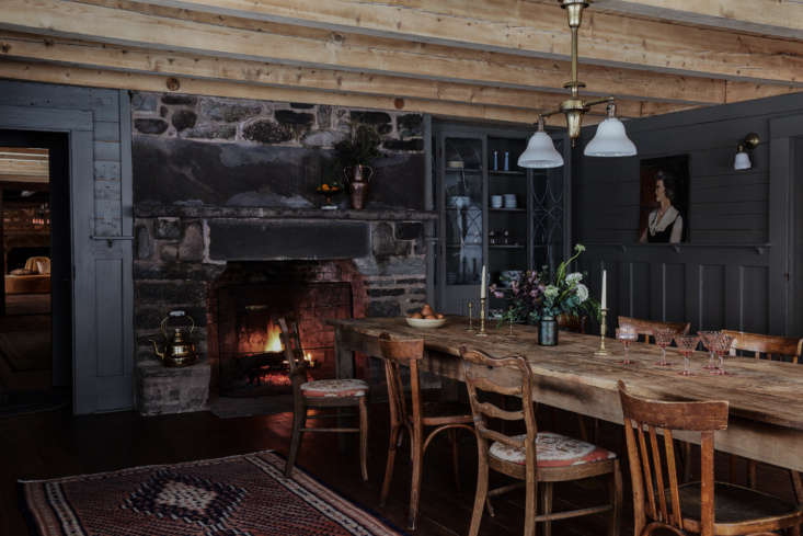 Surrounded by more original paneling, here painted Benjamin Moore Devonshire Green 89, the cozy dining room feels like a rustic tavern. The vintage farm table and chairs are another Brimfield find, while the antique light fixture is fromFed-On Lights in Saugerties, New York.