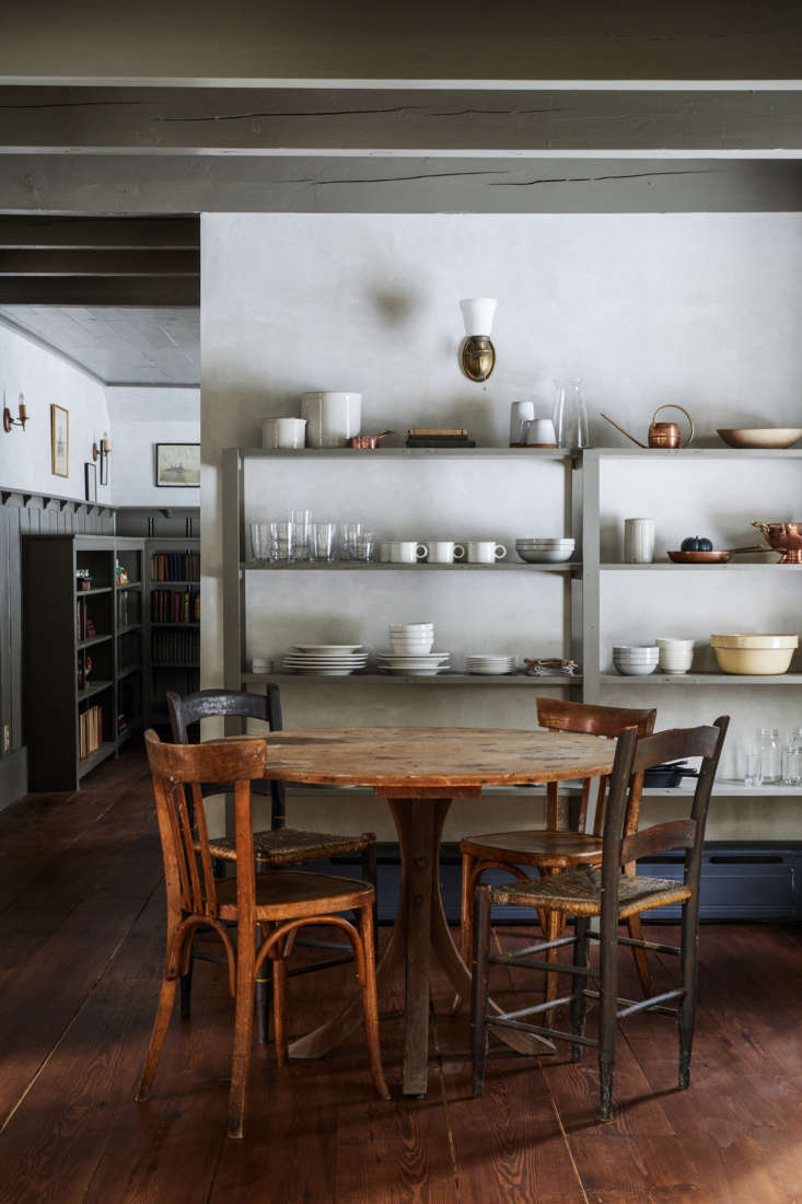 Hand-built open shelving, also painted green, frames the antique dining table and chairs in an L-shape. Photograph by Nicole Franzen from An Arts and Crafts Icon Reborn in the Catskills by Jersey Ice Cream Co.