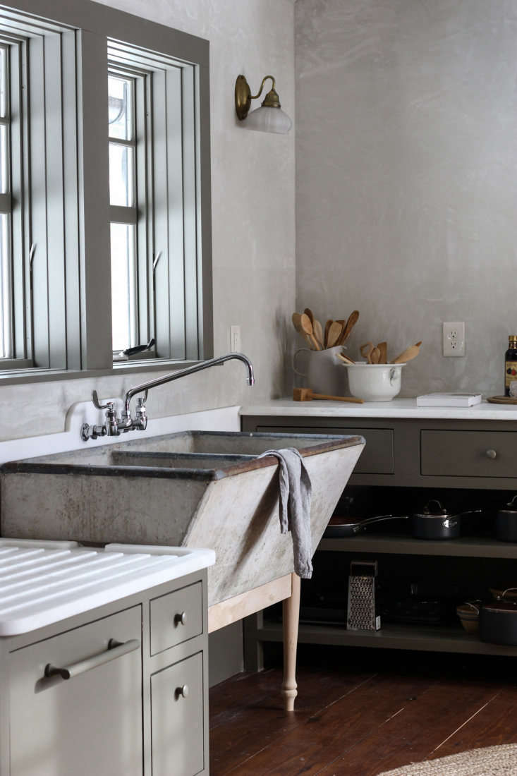 a vintage soapstone laundry sink is hoisted up onto pedestal legs made by percy 10