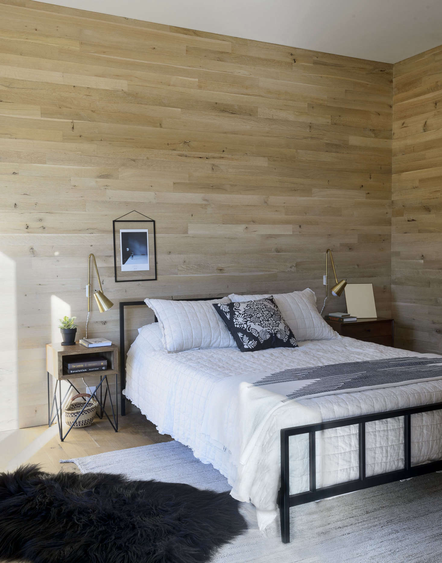 The flooring (and much of the ceilings and walls) is oak. Brass accents can be seen throughout the home, including in the guest bedroom, where brass Wallace sconces byonefortythree flank a black Alchemy bed from CB