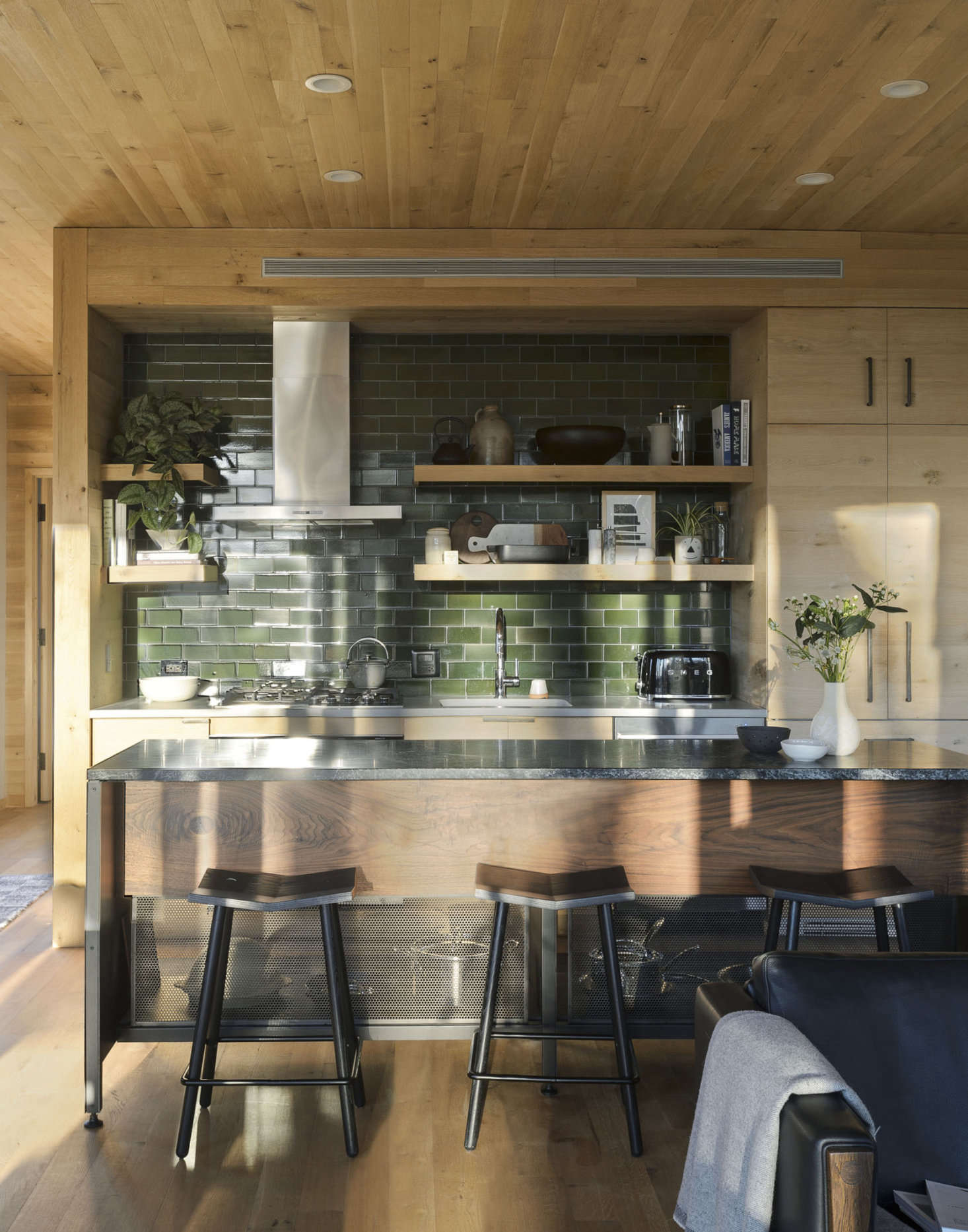 Tucked into the walnut kitchen island are Mitre stools from Souda. The appliances are by Fisher & Paykel.