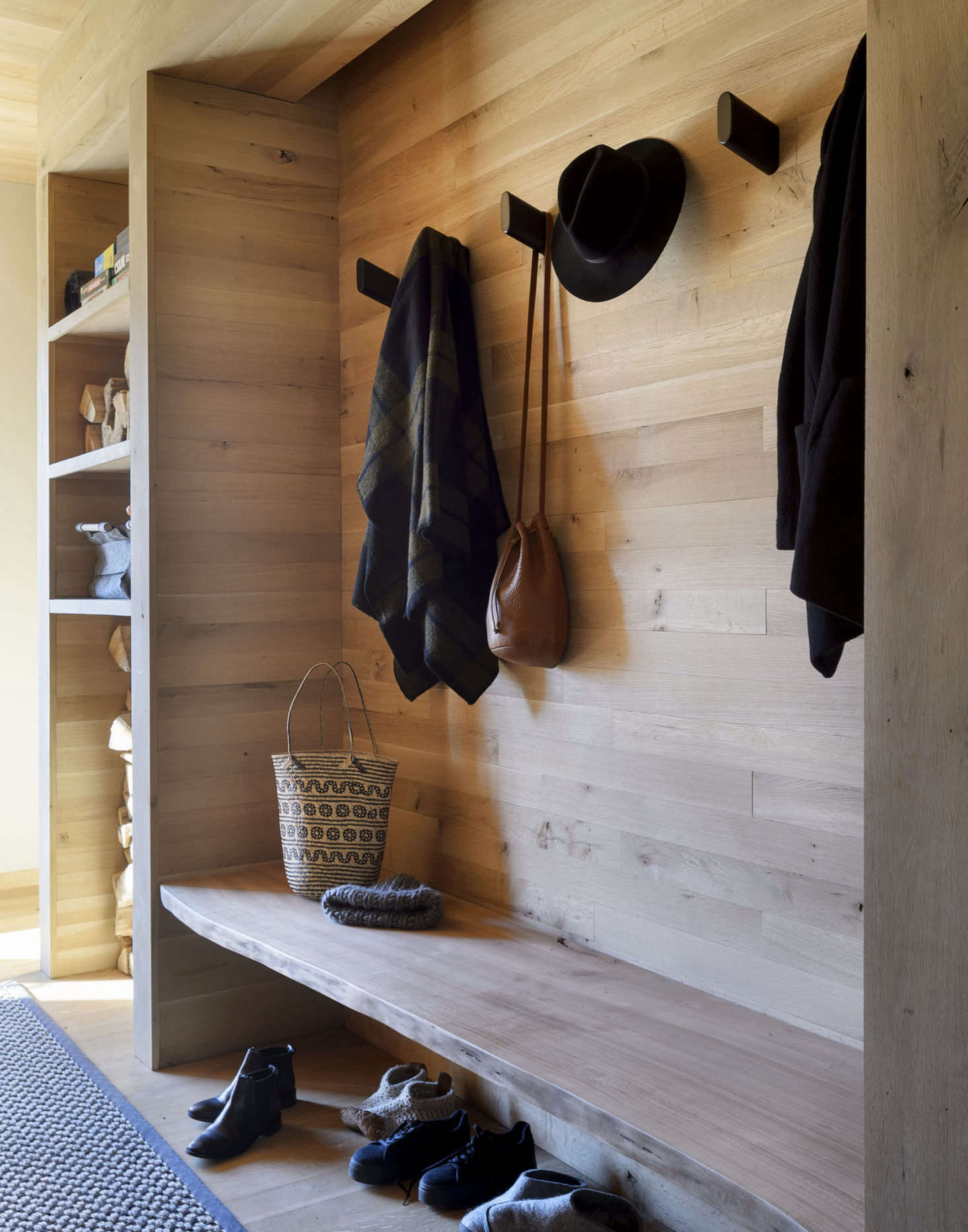 A built-in bench in the entry. The Wook wall hooks are by Blu Dot.