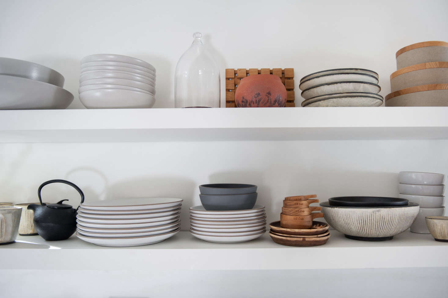 The shelves display plates from Heath and covered bowls by Hasami.