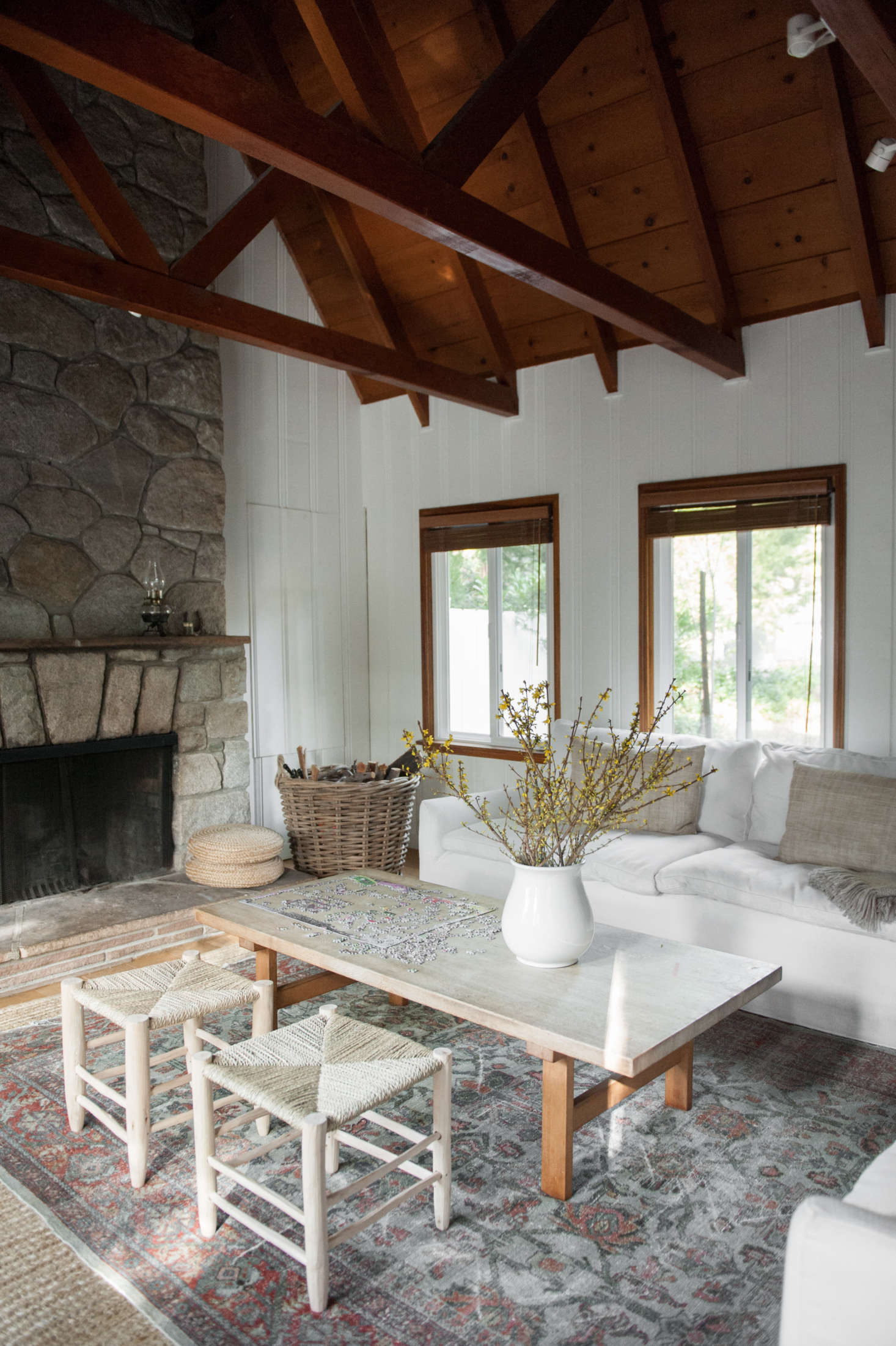 The stone fireplace is original and gets put to use year-round. Lauren placed a patterned carpet over a sisal base: &#8