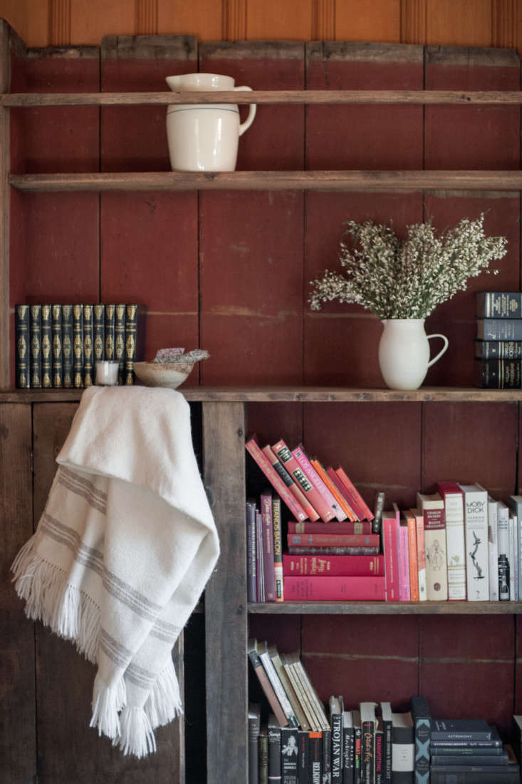 in the guest room, a painted bookcase found at brenda antin antiques holds lean 20