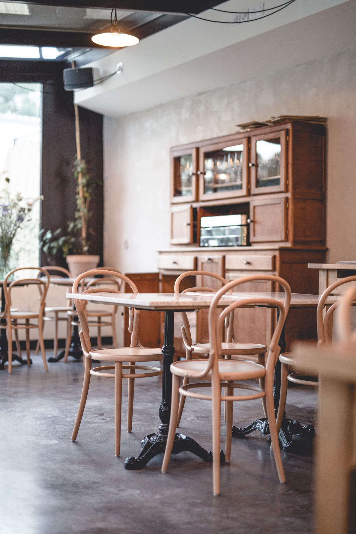 Thonet bentwoodEra Chairs(in a rarely seen natural finish) are mixed with marble-topped cafe tables and an antique sideboard.