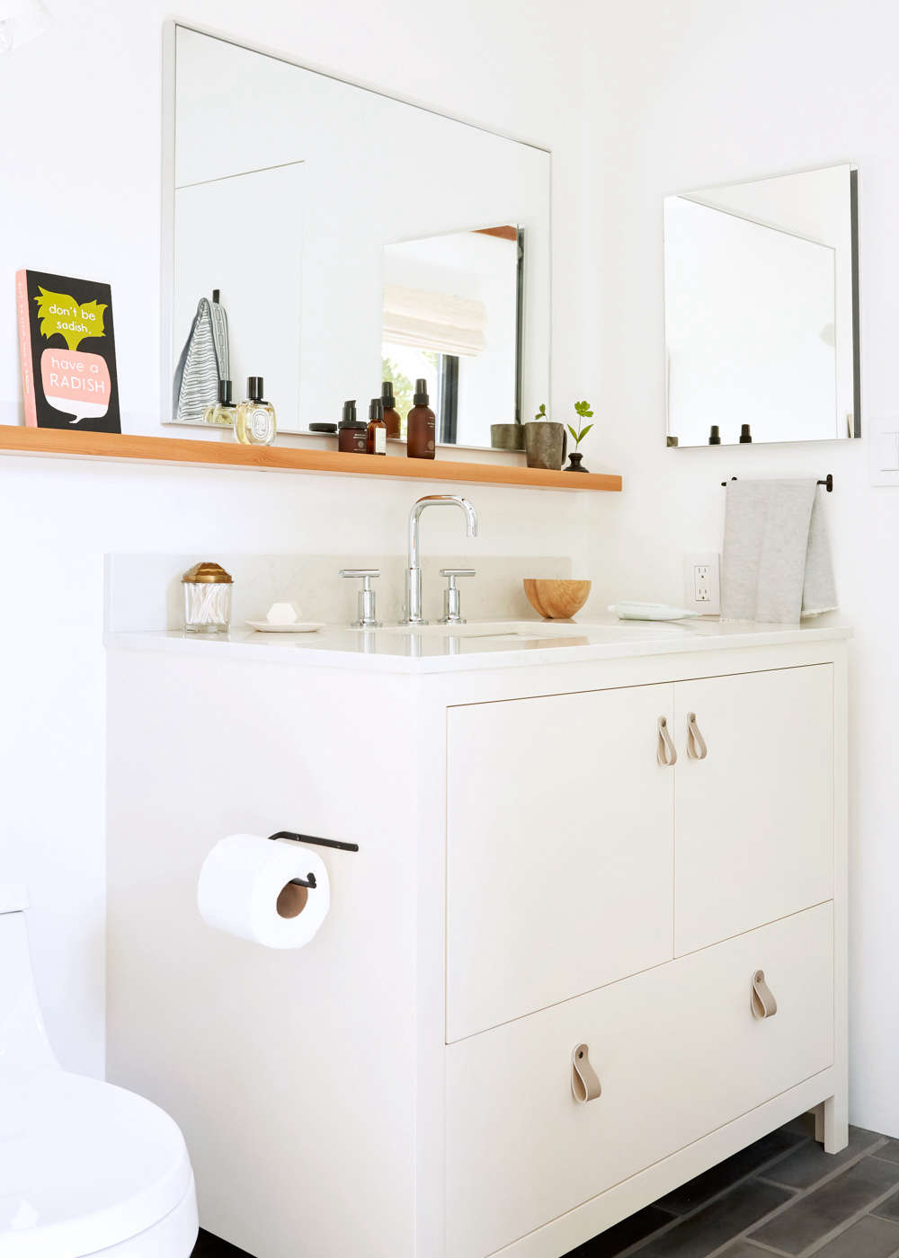 The toilet is theSan Souci K-4007 in white from Kohler, and the Fog Linen Toilet Paper Holder is from Atomic Garden.The custom Douglas fir shelves (over the vanity and tub) were made by Christopher Faiss of Born and Built.