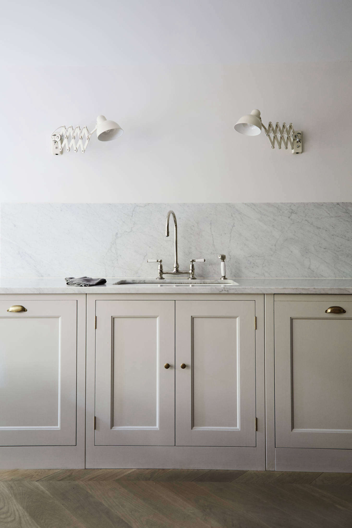The counters are topped with Carrara marble that continues as a backsplash. All of the faucets throughout the house are Barber Wilsons designs—and like the kitchen, the owner had them sent from London: &#8