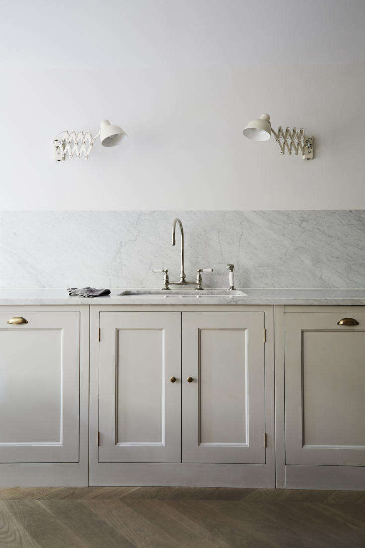 the counters are topped with carrara marble that continues as a backsplash. all 12