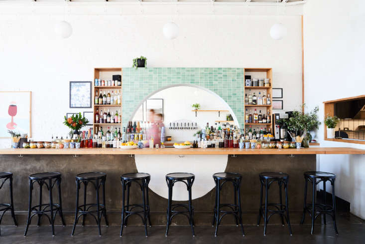 East Meets West Inside Range Life in California On the opposite wall is a dramatic bar. Behind it is an arch tiled in Heath Ceramics&#8\2\17; Meadow Green tiles; the bar itself is made of concrete surfaced withVanilla Bean tile, also by Heath Ceramics. The half circle designs are a reference to Sun Tunnels, an environmental art installation in Utah, and to the Livermore landscape.
