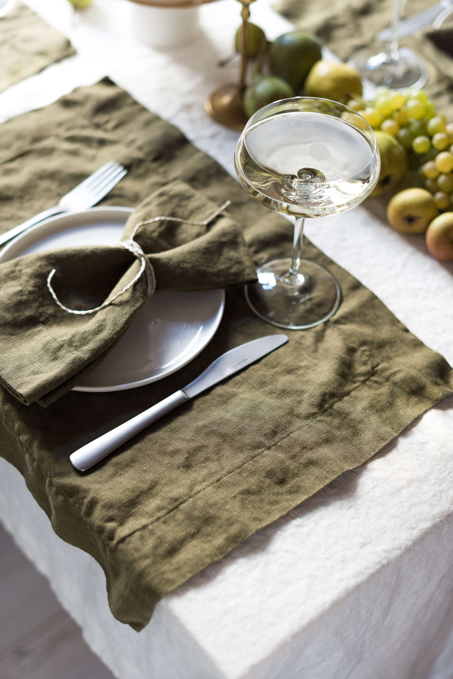 A detail of the place setting, with placemats left to overhang the table just slightly.