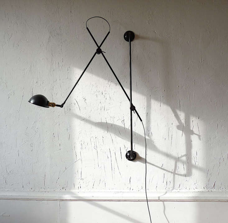 Made in Villeurbanne, France, the Adjustable Two-Arm Wall Lamp by lighting atelier Wo & Wé is made of black steel, and is comprised of a black rod affixed to the wall with articulating arms attached. It&#8