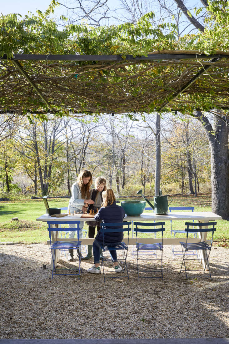 French doors in the back of the house open to a gravel patio shaded by a wisteria arbor: &#8