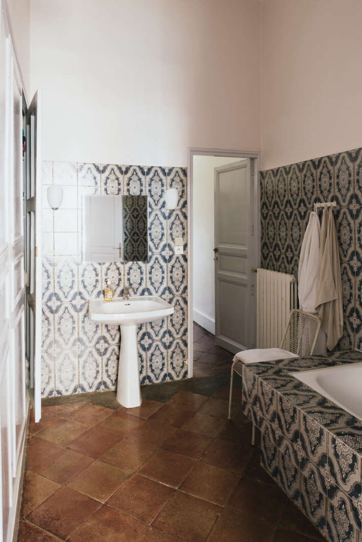 A bathroom with intricately patterned tile and a terra cotta floor.