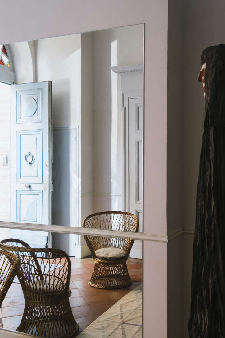 La Vie en Rose Inside a Costumiers Dreamlike DIY Maison in France Stepping into the house, entrants are greeted by a cheerful blue door, a rattan chair, and panels of mirrors.