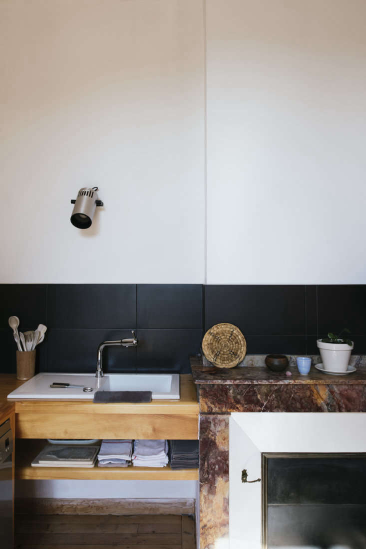 A sink, fitted into a wooden counter. Above it is an old projector light, a nod to Sathal&#8