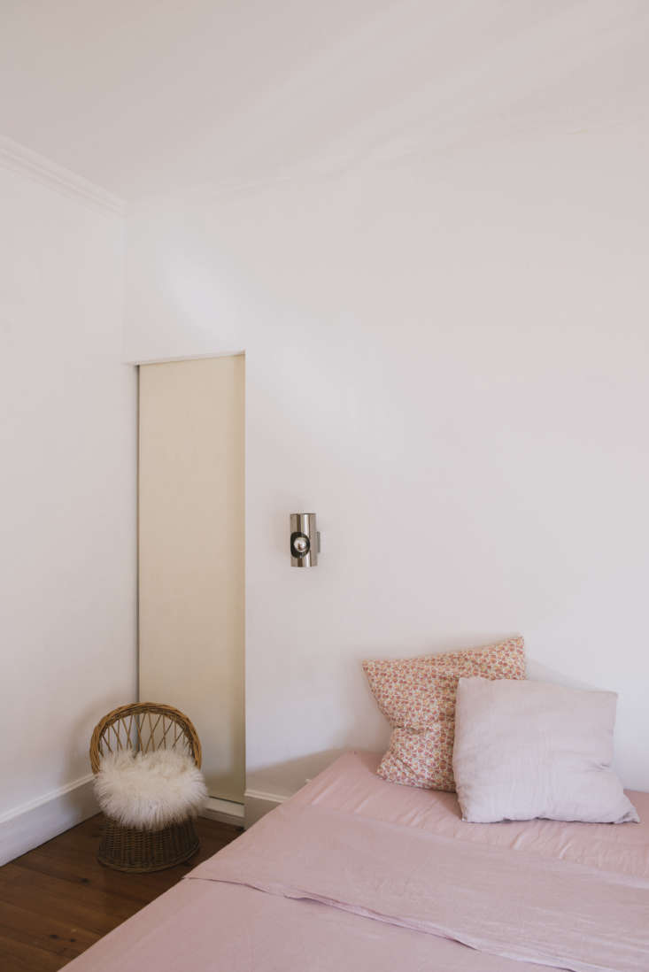 A bedroom with pink linens and silver wall sconces. &#8