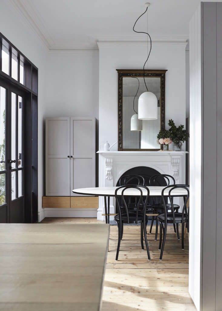 In the dining room, the original fireplace had been replaced by a modern version. Tom and Soma, in turn, replaced that with a mantel dating from the same period as the house. Whiting flanked it with storage cabinets in Dulux&#8