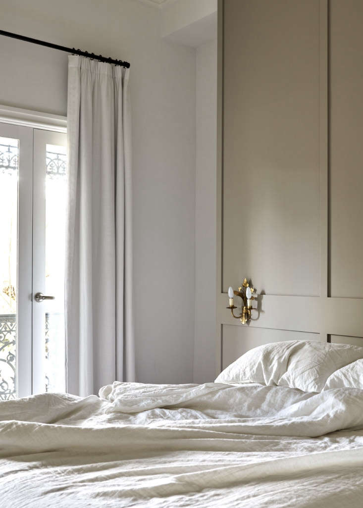 French doors open to the front balcony. Tom and Soma bought the antique sconces on a trip to Paris. The linen bedding is by Bedouin Society.