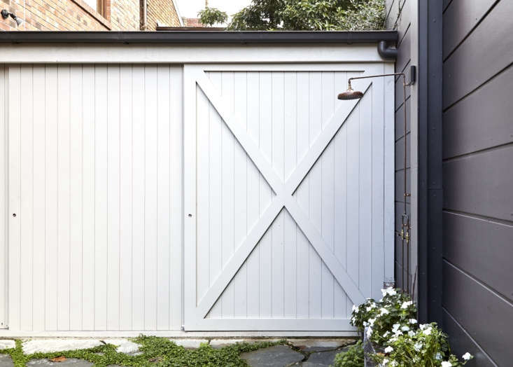 In place of a carport, the backyard now has a flagstone courtyard with a copper outdoor shower that gets used year round. The barn-door shed—made from the same style of paneling used indoors—holds bikes and gardening gear.