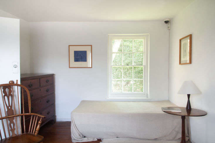 The upstairs bedroom has a basic mattress and frame with a large linen sheet tossed over the top and barely tucked in at the bottom.
