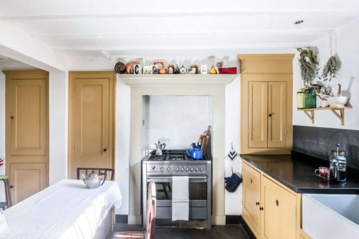 the modest kitchen on the ground floor features ochre paint on the cabinets, a  10