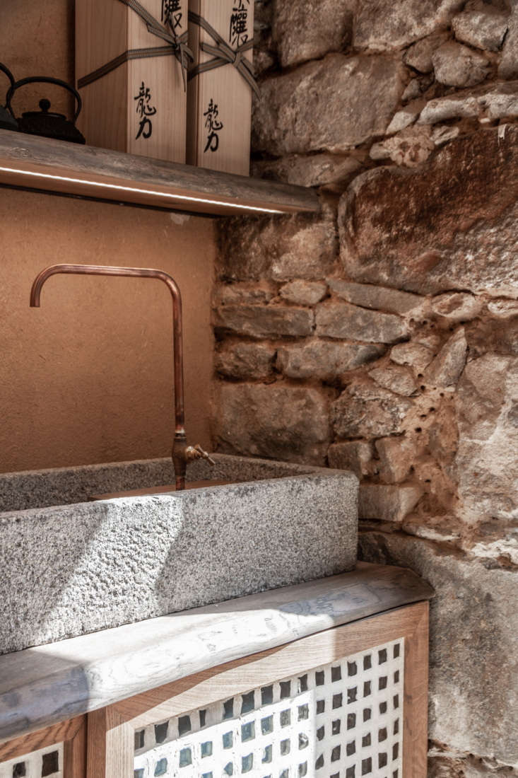 A hand-hewn copper tap anchors a sculptural granite sink.