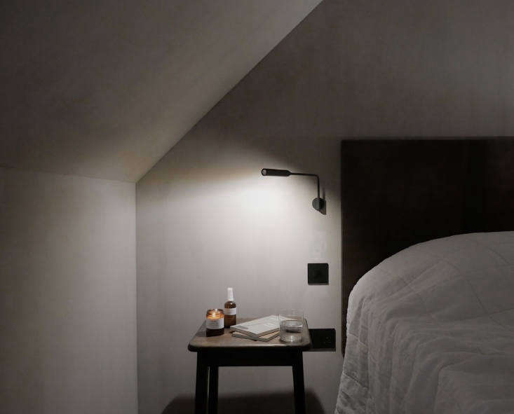The beds have custom leather headboards and bedsideFlo LED Wall Lights by Foster & Partners. On the side tables: reading materials as well as naturally scented candles and &#8