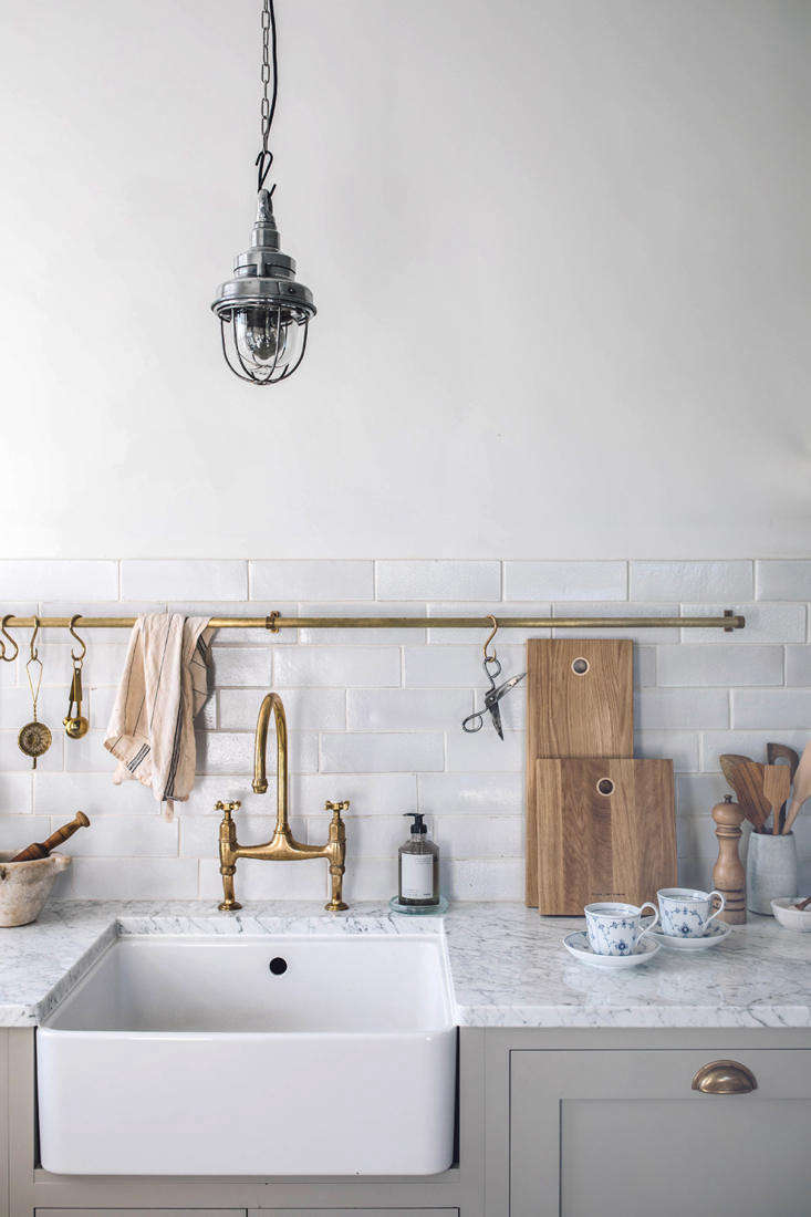 In addition to theFarmhouse Sink, deVol also supplied theAged Brass Ionian Tap, Brass Cabinet Hardware, handmade Crackle Metro Tiles, and Brass Hanging Rail.