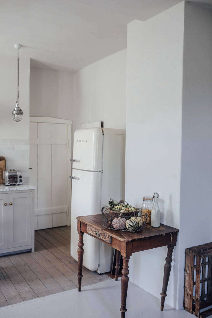 A Smeg fridge is tucked in the back, next to doors to the dining room and WC. The existing flooring was preserved and upgraded: it&#8\2\17;s a combination of old wood (newly finished with gray linseed oil) and painted concrete.