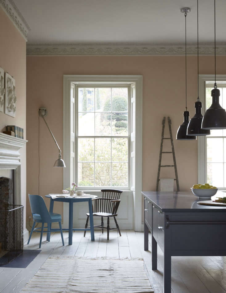 Invitingly small-scale, the breakfast corner is furnished with a Howe replica of an Arts and Crafts Round Oak Table and its Camembert Chair, both in a surprise bright blue. A French apple picking ladder is used as a sculptural dish towel rack.