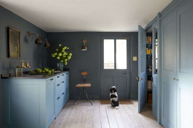 The breakfast table blue,Blue Gum, reappears in the Plain English-furnished pantry offset by walls in Squid Ink(both colors are from Paint & Paper Library). The back door leads to the garden.