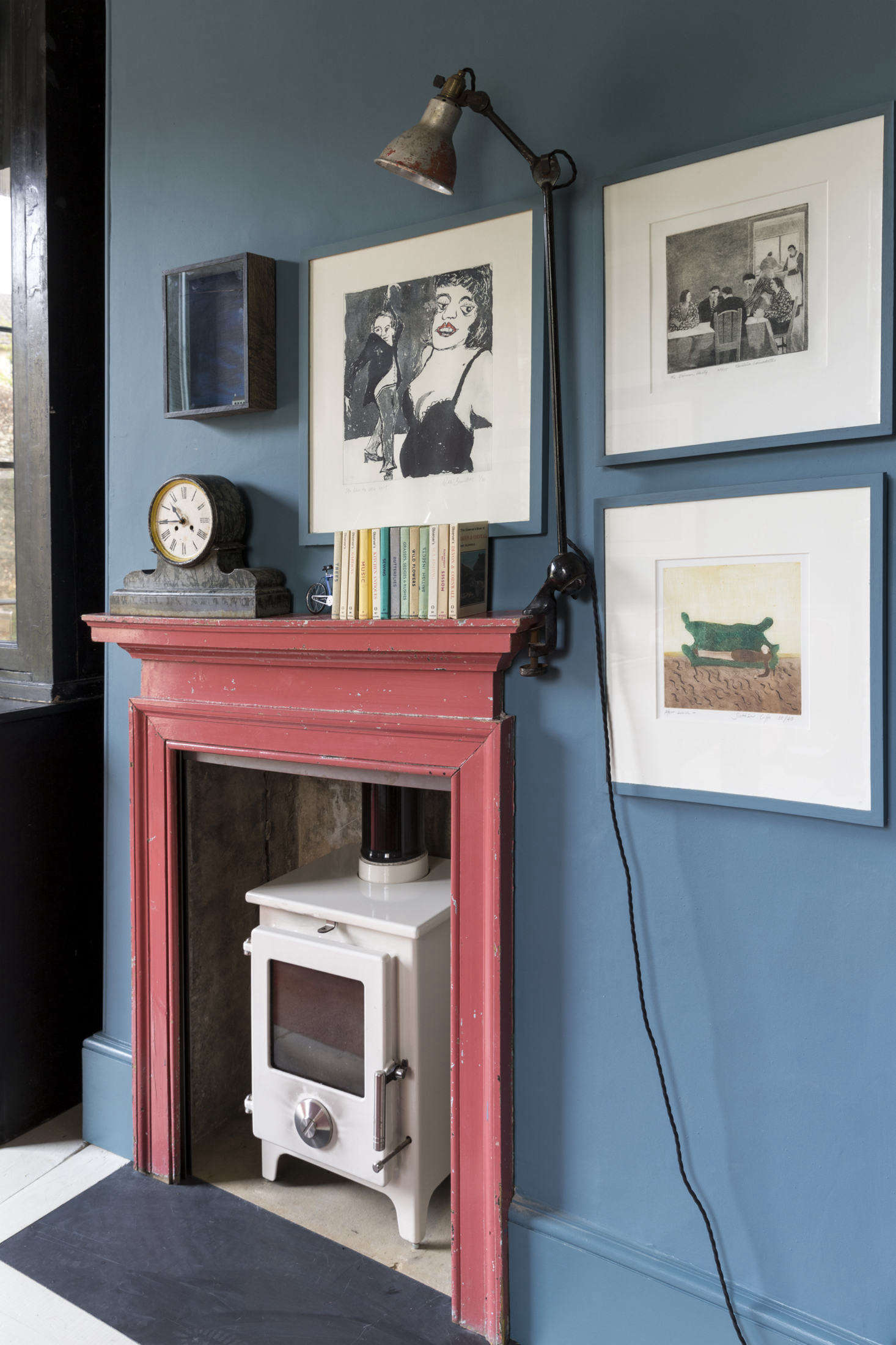 An antique mantel in its original paint was added to the room along with a wood-burning stove and vintage workman&#8