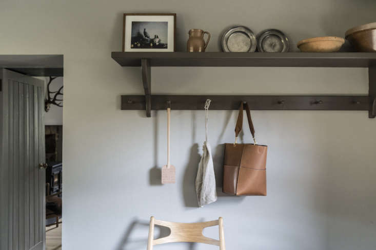 Along one wall, a peg rail and shelf in olive green.