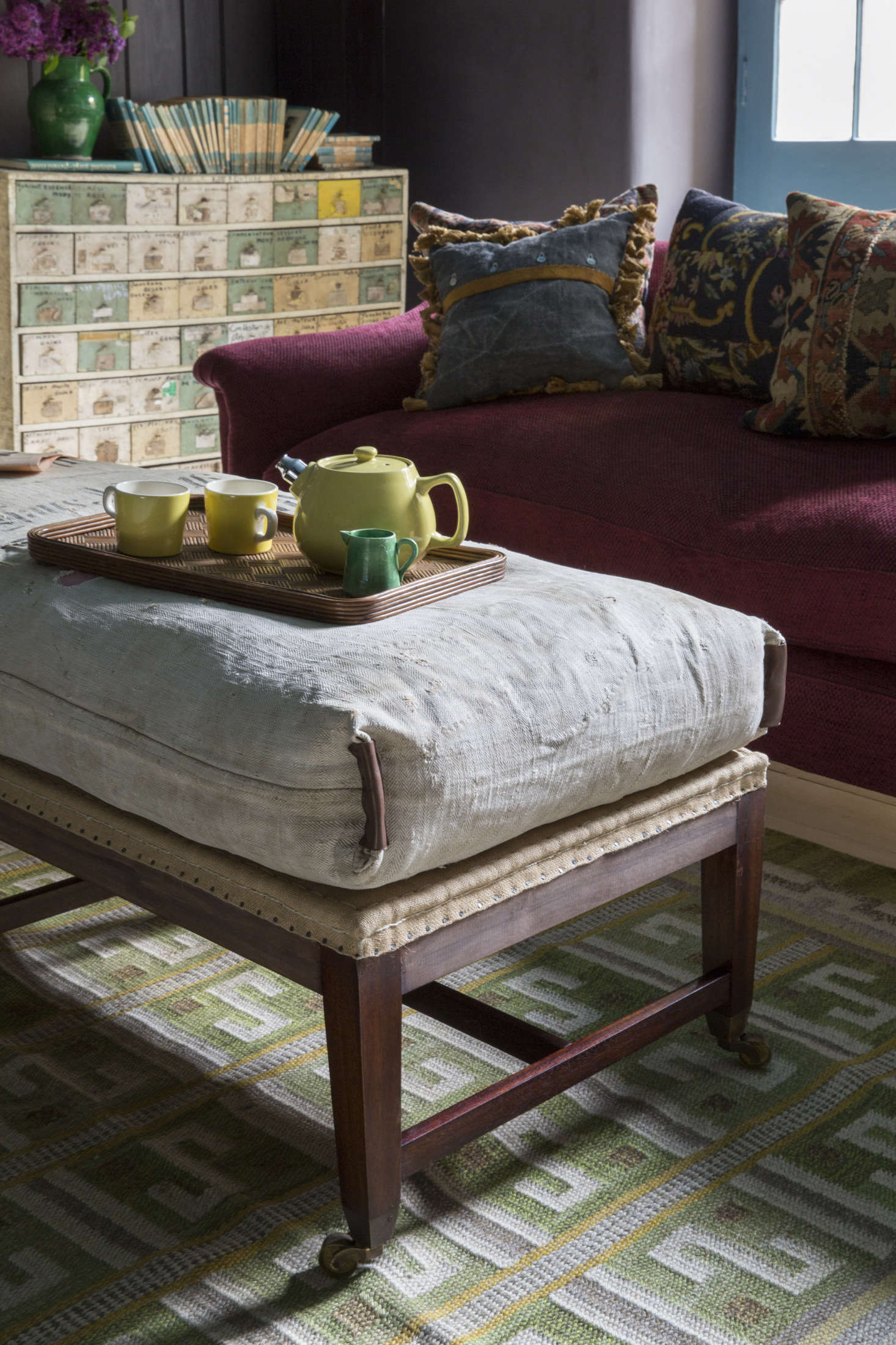 A Howe bestseller, the deconstructed Gainsborough Stool, serves as a seat, footrest, and coffee table. Howe says the set of painted drawers next to the fireplace came out of a Vespa shop in France with labels intact. They&#8