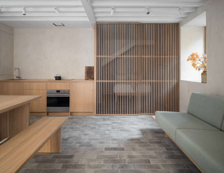 The gray limestone tiles—with radiant floor heating—echo the cobblestones outside.In the back of the room, a second slatted wood screen divides the bedroom from the rest of the quarters.