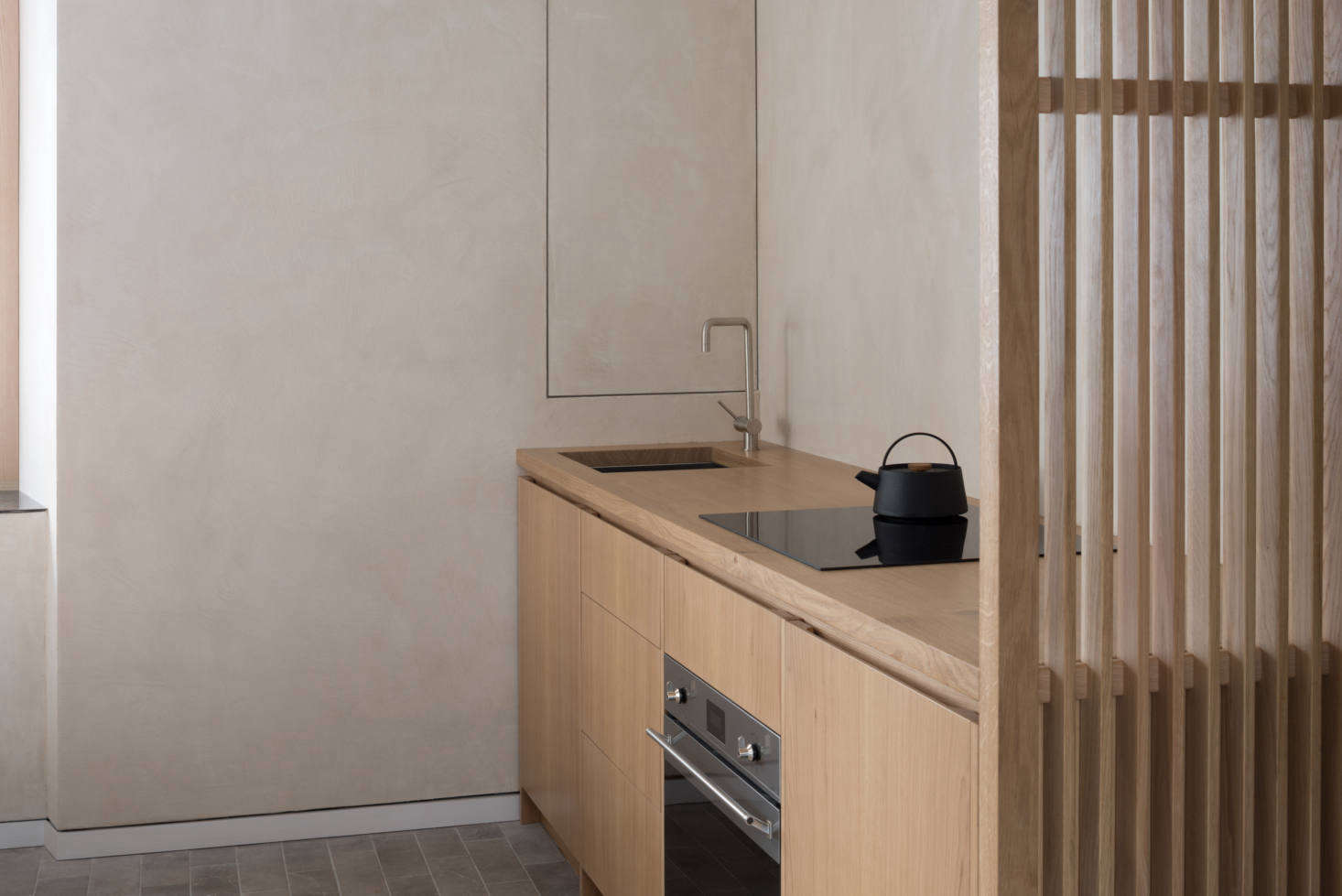 An oak screen neatly divides the kitchen from the bedroom.