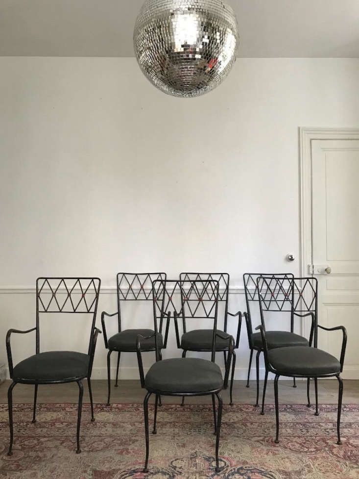 A suite of Six Metal Armchairs with fabric seats have as striking silhouette against a white wall.