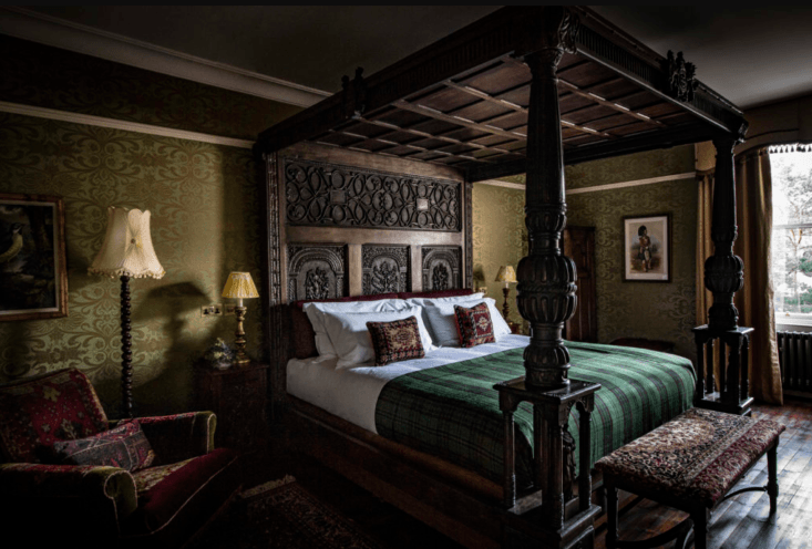 The 46 guest rooms and suites range from lush and jewel-toned to simpler. Here, one of the Royal Suites features a carved canopied bed.
