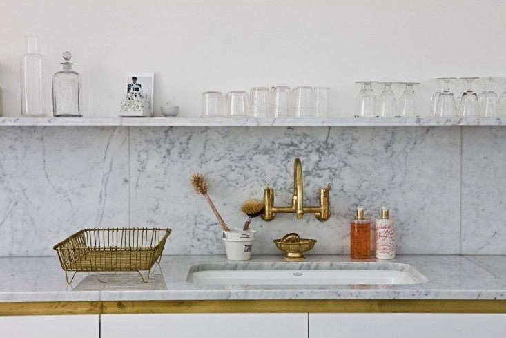 Unlacquered brass fixtures add warmth to the Carrara marble countertops, backsplash, and shelf inSteal This Look: A Glamorous London Kitchen in Marble and Brass.Photograph byHenry Bourne.