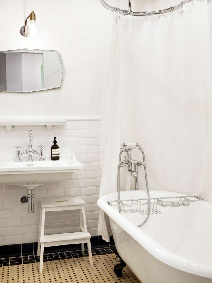 Designed back when the family first moved into the building, the bathroom has a tile rug, a polished nickel bridge faucet, and walls in lined in metro tiles—beveled subway tiles. Thinking of installing your own freestanding tub? See  Things Nobody Tells You About Clawfoot Bathtubs.