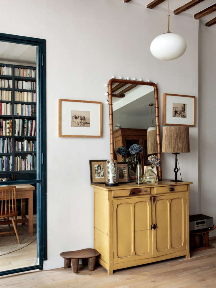 An ensemble of flea market pieces: Hermand frequents the St. Ouen Marché aux Puces. She uses African stool as low tables. The steel door frame is in a powder-coated blue to match the library.