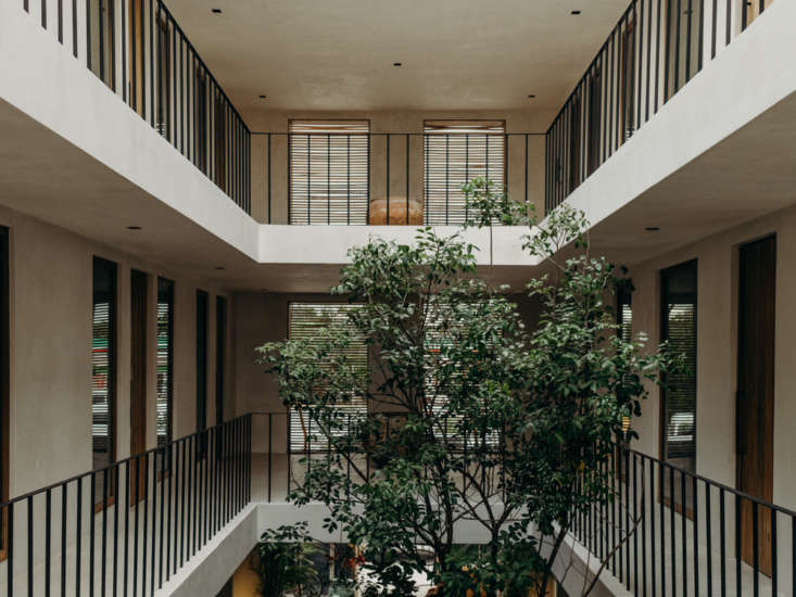 Two stories of rooms surround the atrium. Windows feature slatted wooden shutters.