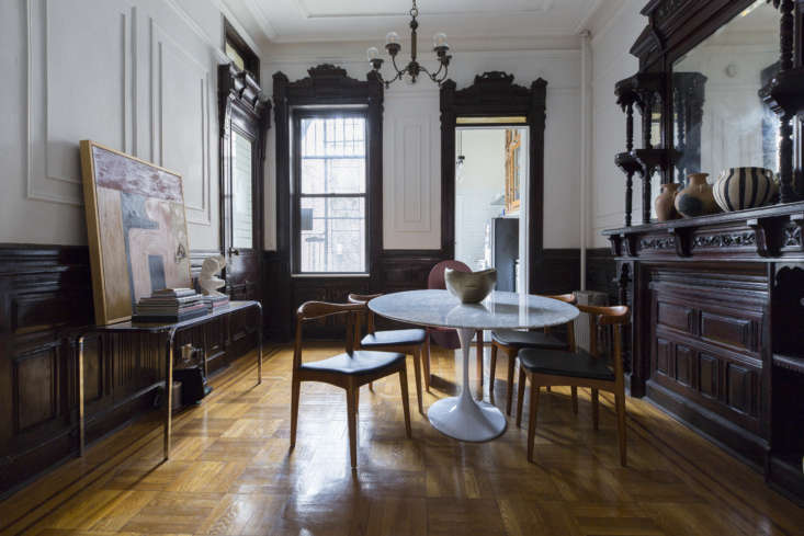 The front door of the apartment opens into the dining room, with dark, original molding and moody light. &#8
