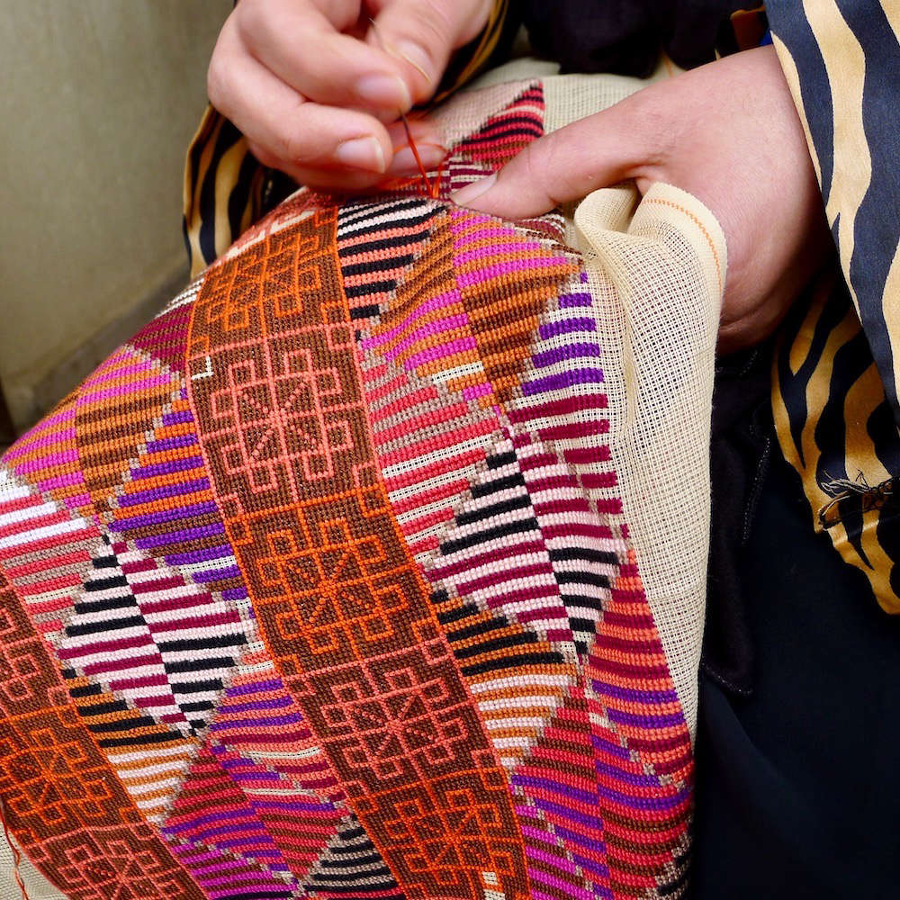 No pattern is printed on the canvas; the craftswomen either consult images of the design or embroider from memory.