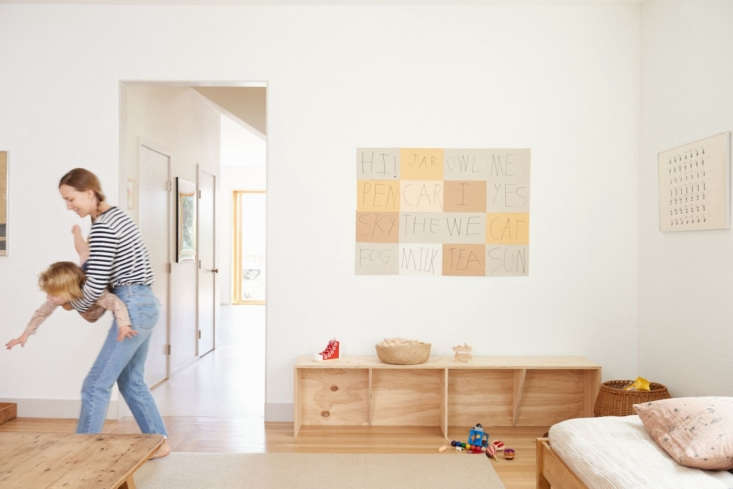 lena wrangles her 4 year old, abe. the artwork above the custom plywood bench b 12